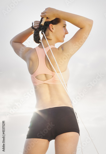 Caucasian woman standing with jump rope