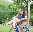 Caucasian couple riding bicycle together