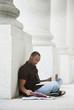 Black college student doing homework outdoors