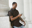 Black college student text messaging on cell phone