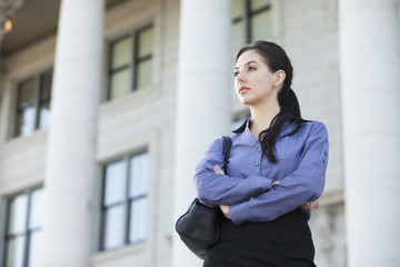 Caucasian businesswoman standing outdoors with arms crossed