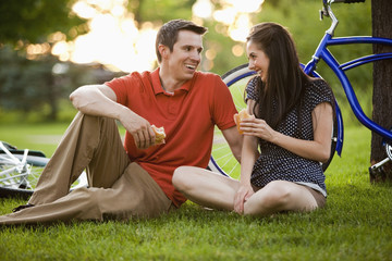 Caucasian couple sitting in grass eating lunch