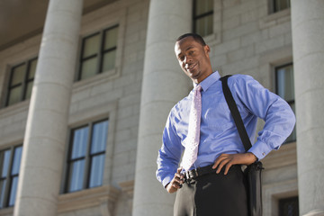Black businessman standing outdoors with hands on hips