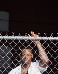 Black man leaning on chain link fence