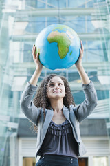 Caucasian businesswoman lifting globe