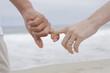 Hispanic couple holding hands on beach