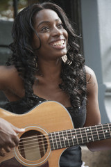 African American woman strumming guitar
