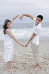 Hispanic couple making heart shape with arms on beach