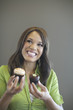 Mixed race woman holding cupcakes