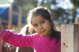 Serious Hispanic girl playing on playground