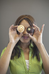 Mixed race woman holding cupcakes in front of her face