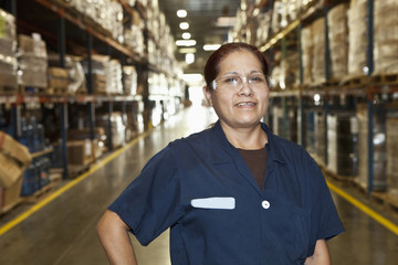 Mixed race woman standing in warehouse aisle