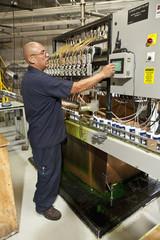 Hispanic worker operating factory control panel