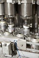 Close up of metal bottles on assembly line