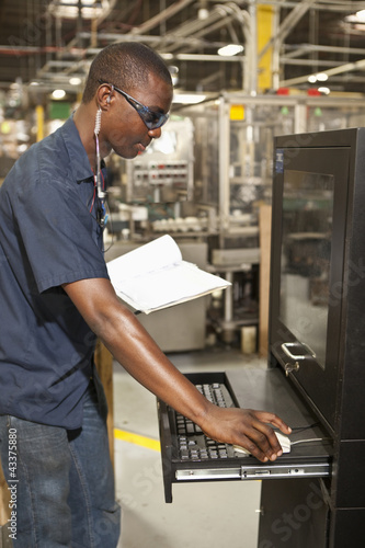 Black worker operating factory computer