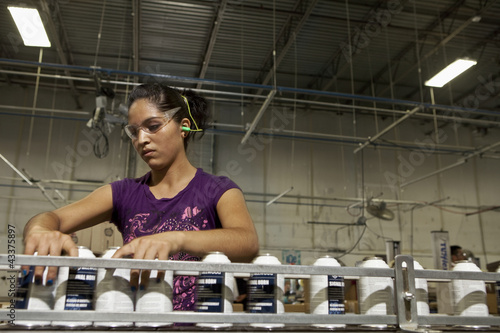 Hispanic worker holding cans on assembly line