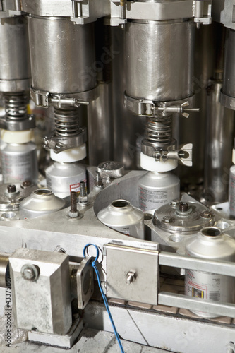 Close up of metal bottles on assembly line