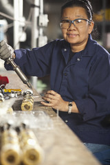 Asian woman working in electronics factory
