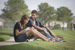 Mixed race teenage couple sitting in grass