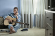 Mixed race teenager holding guitar and talking on cell phone