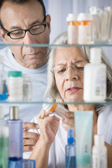 Hispanic couple in bathroom checking prescription