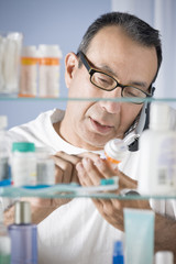 Hispanic man talking on phone checking prescription