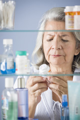 Hispanic woman looking at prescription in bathroom