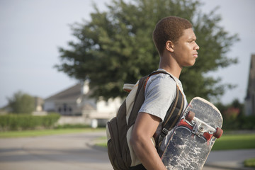 Mixed race teenager carrying skateboard