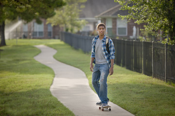 Mixed race teenager riding skateboard on sidewalk