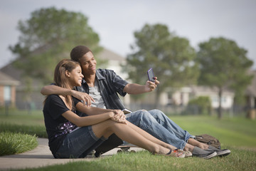 Mixed race couple taking self-portrait with cell phone