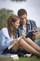 Mixed race couple doing homework with digital tablet