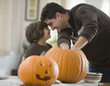 Mixed race father and son carving Halloween pumpkins
