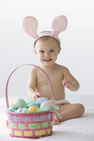 Caucasian baby girl in bunny costume with Easter eggs