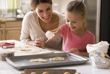 Caucasian mother and daughter making Valentine cookies