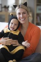 Caucasian mother sitting with baby daughter in bee costume