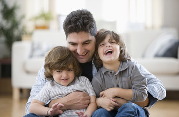 Mixed race boys sitting in father's lap on floor