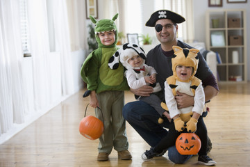 Mixed race father and sons in Halloween costumes