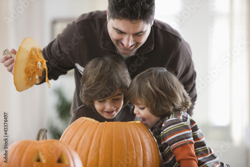 Mixed race father and sons carving Halloween pumpkins