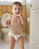 Mixed race baby boy standing in bathroom