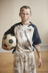Dirty Caucasian boy holding soccer ball