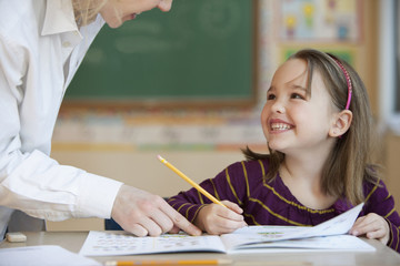 Teacher helping Caucasian girl studying in classroom