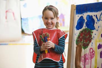 Caucasian girl painting in art class