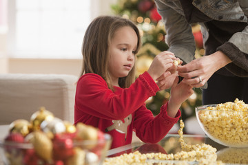 Caucasian girl stringing popcorn with mother at Christmastime