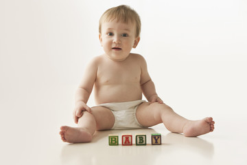 Mixed race baby boy playing with alphabet blocks