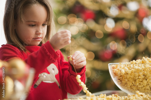 Caucasian girl stringing popcorn at Christmastime