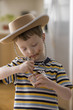 Caucasian boy in cowboy hat eating pudding