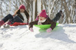 Hispanic girls sledding on snow covered hill