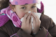 Hispanic girl blowing her nose outdoors in winter