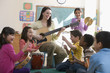 Teacher playing guitar for students in classroom