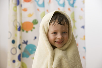 Caucasian boy wrapped in a towel